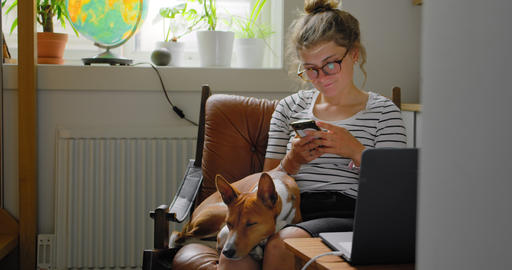 Woman and her dog in comfortable armchair at home Live Action