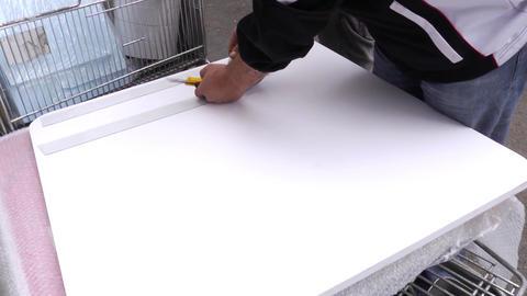 Worker who sticks sticky paper on a polystyrene plate 48 Live Action