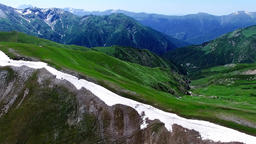 Aerial view mountain valley 4k nature video. Green rocky landscape, snow range Footage