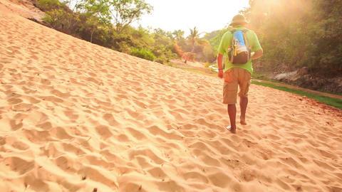 Camera Moves to Tourist Walking along Narrow Fairy Stream Image