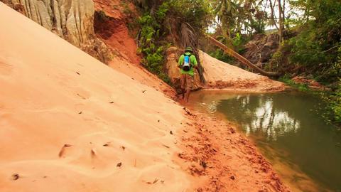 Tourist Walks along Sandy River Bank of Fairy-Stream Footage
