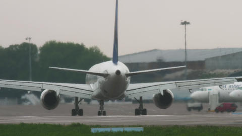 Air Astana Boeing 757 taxiing after landing at rainy weather Live Action
