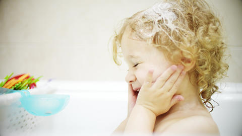Curly blonde baby girl washes her face and hair in bathroom Live Action