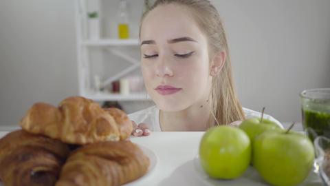 Portrait of beautiful slim girl choosing between green apples and crusty Live Action