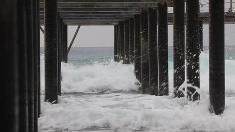 Coming waves beat on steel pier piers. Under pier view. Overcast weather Live Action