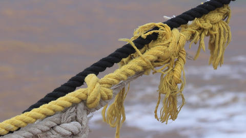 Yellow white and black twisted nautical ropes trembling from waves beats on pier Live Action