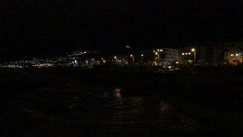 Night Alanya highway traffic with residential buildings lights with splashing waves on the beach Live Action