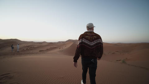 SLOW MOTION: ADVENTUROUS YOUNG MAN WALKING TROUGH DESERT OVER DUNE AND PICKING Live Action
