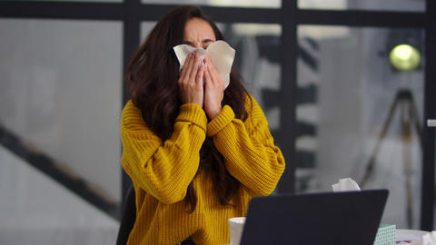 Sick businesswoman getting flu in office. Ill woman sneezing near laptop indoor Live Action