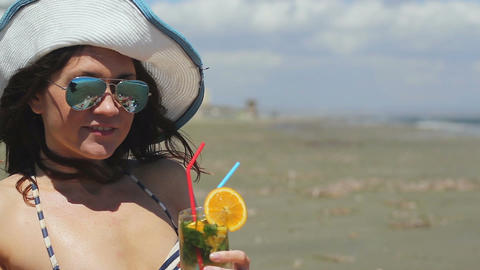 Closeup beautiful woman wearing sunglasses and hat, having long drink on beach Footage