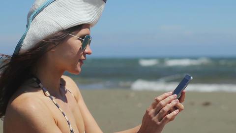 Young woman in bikini making selfie on smartphone, sharing photo on sandy beach Footage