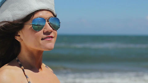 Closeup of young female in sunglasses enjoying relax on sunny beach at seaside Footage