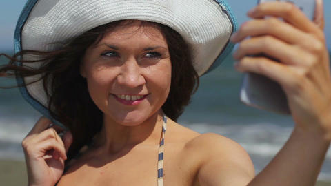 Happy young woman making selfie on seaside beach, taking picture on smartphone Footage