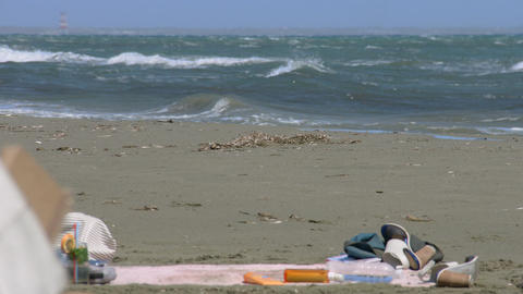Tourists' shoes, clothes abandoned on beach, cold stormy weather, hurricane Footage