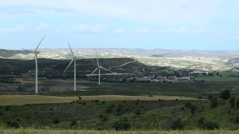 Huge wind turbine propellers rotate in green valley, generate alternative energy Footage