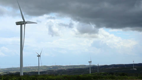 Dark clouds in stormy sky over wind farm, turbine blades rotate, weather change Footage