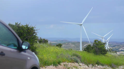 Car near spinning wind turbines, renewable energy source, alternative to fuel Footage