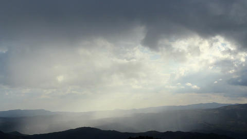 Beautiful rainy dawn in mountains, sunlight rays shining through cloudy sky Footage