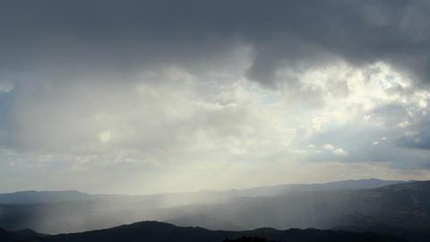 Beautiful rainy dawn in mountains, sunlight rays shining through cloudy sky Footage