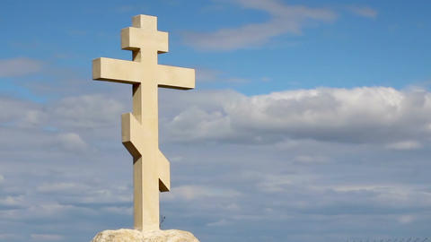 Christian cross on grave stone, peaceful blue sky background, religion, church Footage