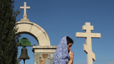 Young woman praying to God with clasped hands, stone cross, religious symbol Footage