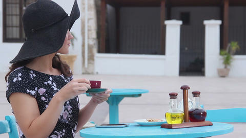Romantic young lady relaxing at luxury resort, drinking coffee, waiting for date Footage