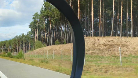 Person driving car, objects on the road reflected in side view mirror. Traveling Footage