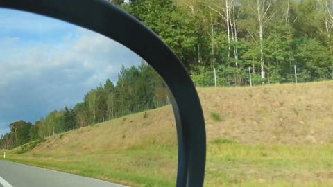 View of the roadside from car passenger seat. Person looking in side view mirror Footage