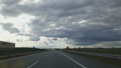 Timelapse of driving on freeway on summer day. Sun hides behind low dark clouds Footage