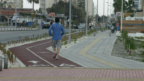 Men running on jogging track along city street. Active lifestyle for fit body Footage