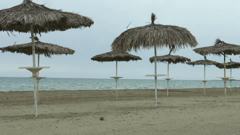 Umbrellas on empty beach. Waves splashing in stormy sea. Off-season at resort Footage