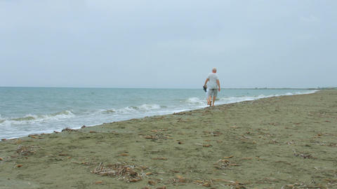 Senior married couple enjoying walk along seaside. Retired people traveling Footage