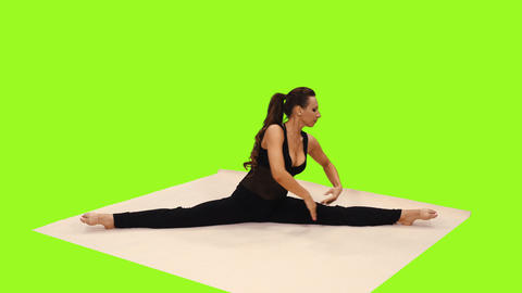 Active brunette female in the splits stretches from side to side, alpha channel Footage