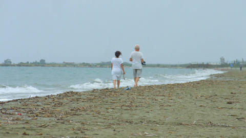 Senior man and woman strolling along sandy beach, enjoying vacation at resort Footage