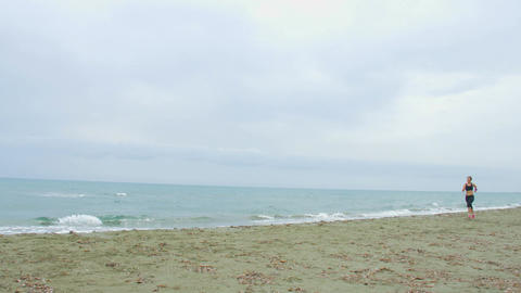 Stormy seaside, gray clouds on horizon. Young brunette female running on beach Footage