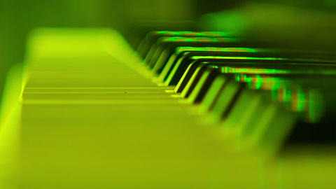 Closeup Electric Piano Keys under Flashes of Colourful Lights ビデオ