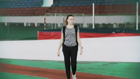 Beautiful athletic woman talks on smartphone in a sport gym or sport arena Live Action