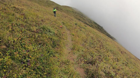 Bicyclist riding on mtb bicycle in misty haze at mountain range trail. Point view tourist biker Live Action