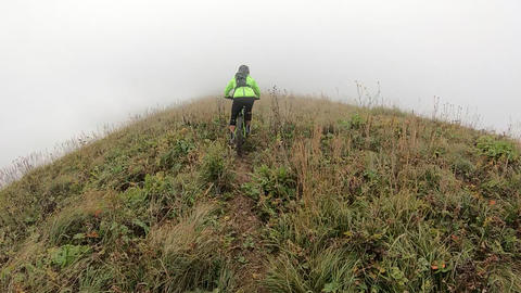 Point view from action camera biker tourist riding freeride on downhill mountain bike at foggy path. Live Action