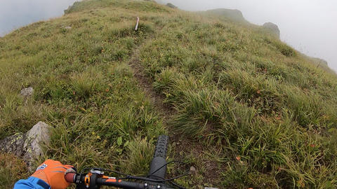 Biker riding freeride on rocky path in foggy mountain point view from action camera. Tourist holding Live Action