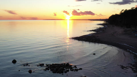 Dron's flight over the coast at sunset, the picturesque sunset, quiet water, a Live Action