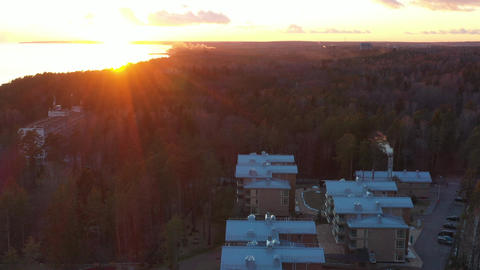 Roofs of houses in the forest, the picturesque coast at sunset, quiet water Live Action