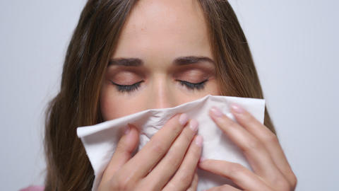 Sick businesswoman sneezing in napkin.Girl with flue looking at camera in studio Live Action