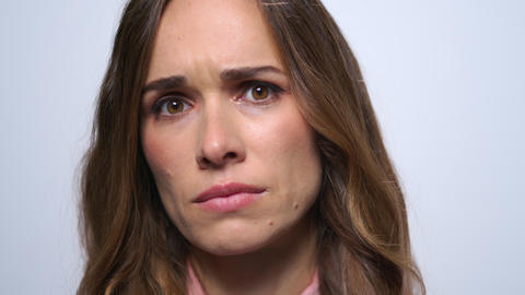 Disappointed woman face looking at camera in studio. Closeup upset girl face Live Action