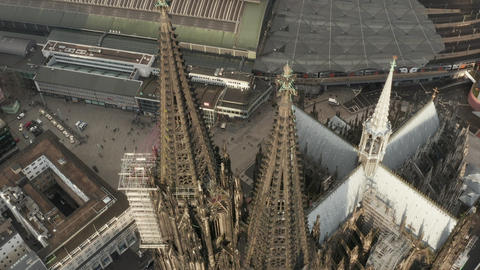 AERIAL: Close Up Overhead Circle around Cologne Cathedral brown Towers in Live Action