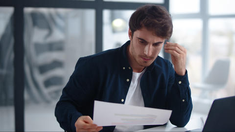 Upset businessman finding mistakes in documents. Sad guy looking papers indoor Live Action