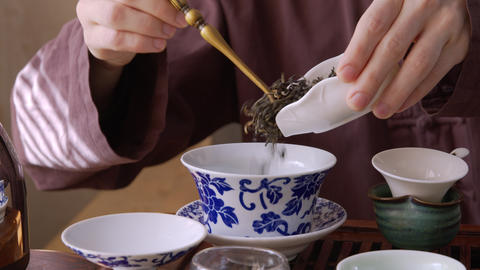 Close up view of male hands pouring tea leaves in tea bowl Live Action