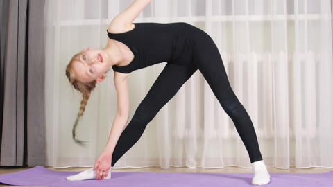 Concentrated sporty teen girl practicing yoga at home GIF