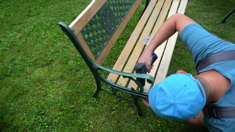 Carpenter man unscrew bolts of retro bench. Renewal process of outdoor furniture Live Action