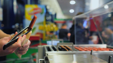 man adds mustard to tasty fresh hot-dog in fastfood cafe Live Action